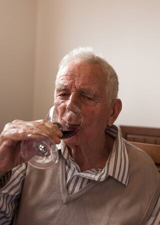 Senior man in shirt and vest drinking red wine from glass at home Stok Fotoğraf