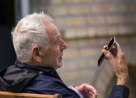 Senior man sitting in backyard and talking on mobile phone