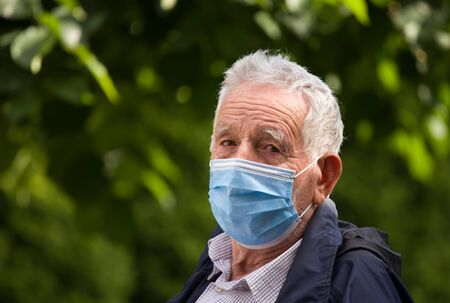 Portrait of senior man with protective facial mask in nature. Safety measures during pandemic