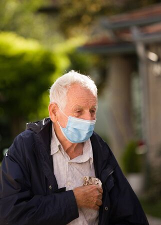 Portrait of senior man with protective facial mask outside of home. Safety measures during pandemic Archivio Fotografico