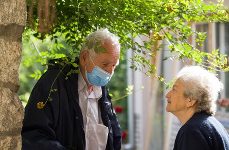 Senior man with mask talking to old woman in neighborhood after pandemic. Safety and protection measures for elderly people Archivio Fotografico