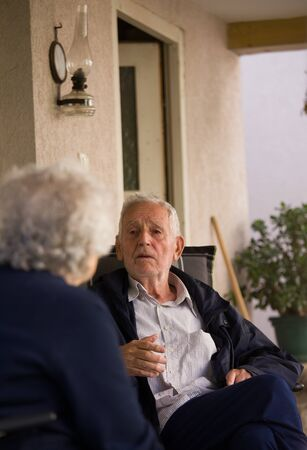 Senior man and woman sitting on terrace and talking in spring time Archivio Fotografico