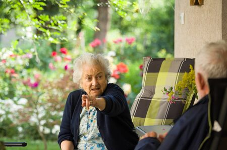 Senior man and woman talking on terrace with beautiful floral garden in background