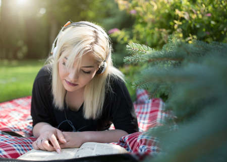 Teenage girl with headphones lying on stomach and reading book on blanket in park in summer time
