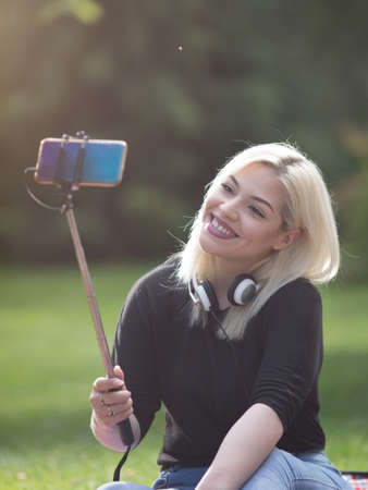 Teenage girl with blond hair taking selfie with mobile phone on stick on picnic in park