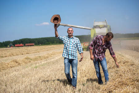Two satisfied farmers walking in wheat field during harvest. Combine harvester working in background Archivio Fotografico