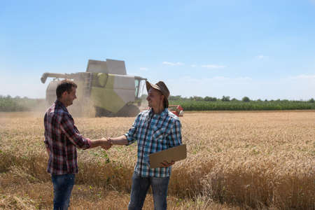 Two farmers shaking hands in wheat field during harvest, with combine harvester in background