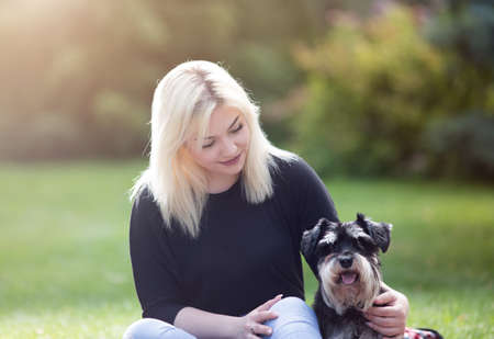 Portrait of blond teenage girl sitting on grass with her dog miniature schnauzer in park in spring time Archivio Fotografico