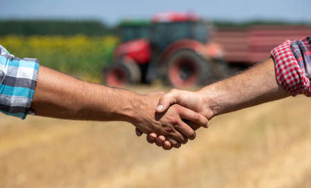 Farmers shaking hands in field in front of tractor with trailer during wheat harvest in summer time