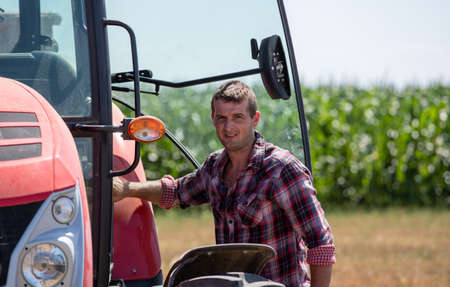 Farmer in plaid shirt entering tractor in field during harvest Archivio Fotografico