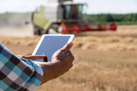 Close up of farmer's hand holding tablet in front of combine harvester working in wheat field