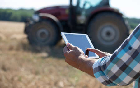 Close up of farmer's hand holding tablet in front of tractor working in wheat field