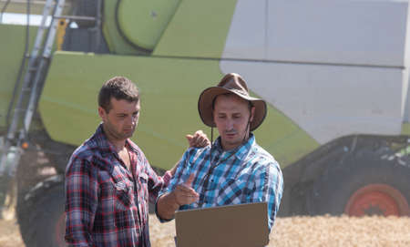 Two farmers looking at laptop in field with combine harvester in background