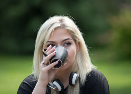 Portrait of pretty blond teenage girl with headset drinking coffee in park Archivio Fotografico