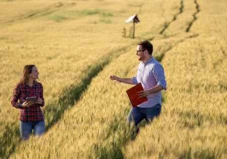 Happy couple enjoying moment in rape barley field, walking and loughing