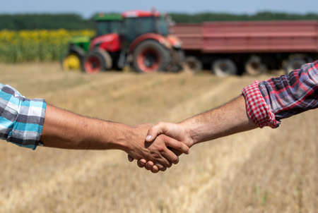 Farmers shaking hands in field in front of tractor with trailers during wheat harvest in summer time