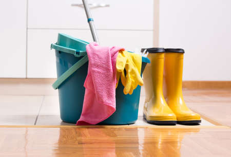 Bucket, mop and gumboots standing on floor in front of kitchen cabinets. Hygiene and house keeping concept Stock Photo