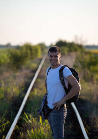 Handsome man with backpack standing on rails, ready for adventure