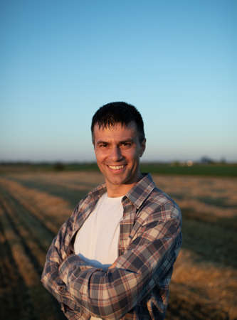 Handsome farmer with crossed arms standing in field during harvest Archivio Fotografico