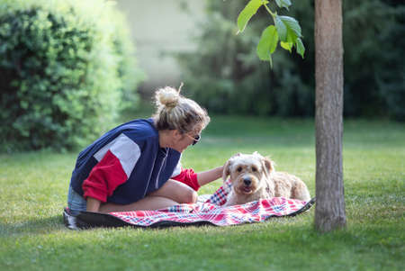 Pretty young girl sitting on blanket in park and cuddling her cute dog Archivio Fotografico