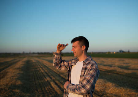 Handsome farmer standing in field during harvest, holding hand above eyes to block sun Archivio Fotografico