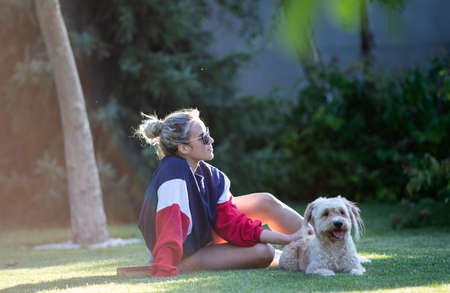 Pretty young girl sitting on grass in park and pet her cute dog