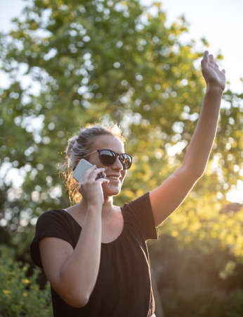 Pretty young girl talking on mobile phone and waving hand in park Archivio Fotografico
