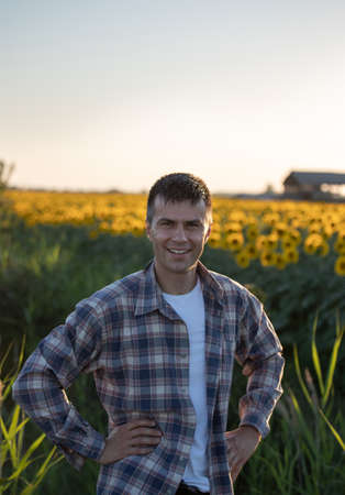 Portrait of handsome farmer standing in front of sunflower field at sunset in summer time Archivio Fotografico