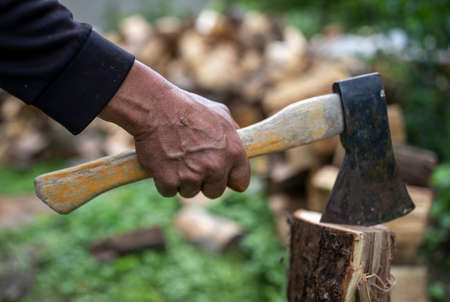 Close up of old man's hand holding ax and splitting woods in backyard Archivio Fotografico