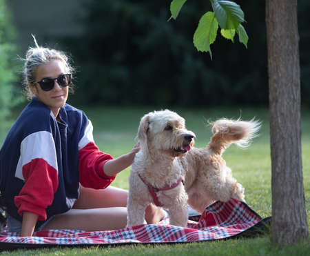Pretty young girl sitting on blanket in park and pet her cute dog