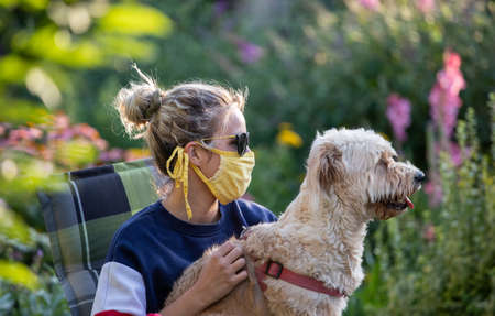 Pretty girl with facial mask holding cute dog on lap in garden. Social distancing concept