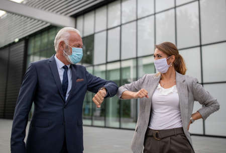 Business man and woman with safety masks greeting with elbow bump in front of office building. Virus protection concept