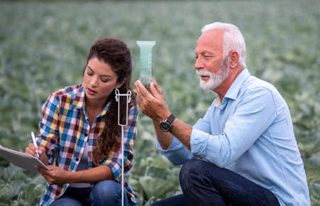 Mature farmer looking at rain gauge in field while young woman assistante writing down measures