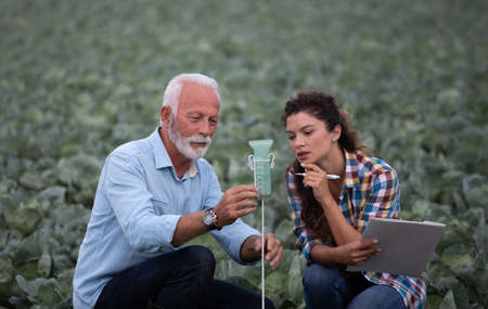 Mature farmer and young woman assistante looking at rain gauge in field
