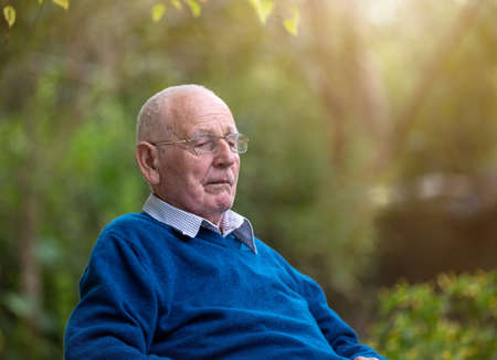 Portrait of senior man with eye glasses sitting in park.