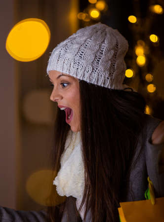 Excited pretty young girl with shopping bags on elbow looking at shop window. City christmas lights in background