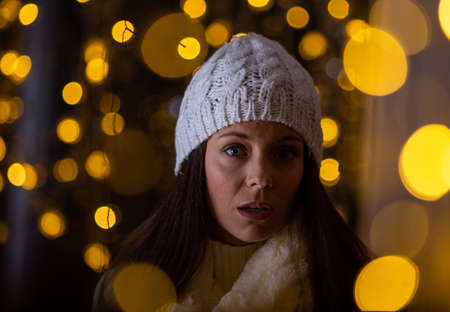 Pretty young girl in coat with white cap walking on street with christmas lights around and looking at shop window