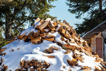 Log pile covered with snow behind village cottage in mountains