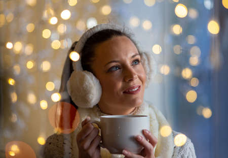 Beautiful girl with earmuffs holding cup of hot coffee with christmas lights in background. Festive moments concept