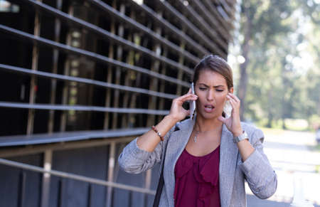Stressed young business woman talking on mobile phone in front of office building