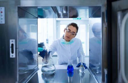 Pretty young biologist working with chemicals in bottles. Shoot from inside of incubator