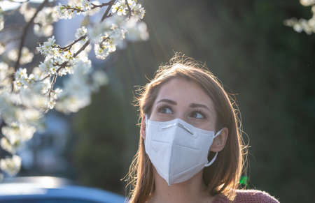 Young woman with facial mask standing in front of blooming tree in spring. Pollen allergy protection