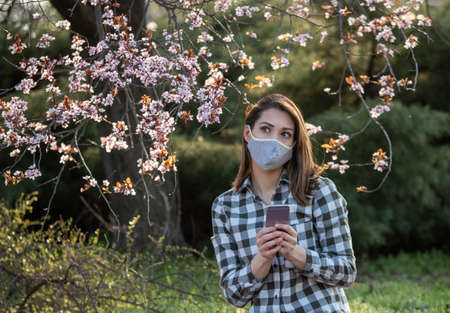 Pretty girl with facial mask holding mobile phone in nature in front of blooming tree. Spring allergy concept