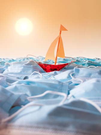 Safety surgical masks arrangement with metaphor of sailing boat on waves on open sea with sunset in background. Summer holiday concept in pandemic era Archivio Fotografico