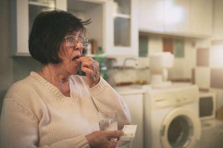 Senior woman sitting in kitchen and drinking pills