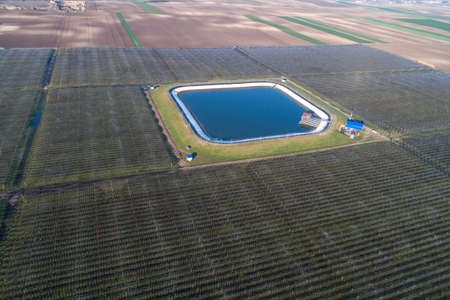 Aerial image of modern apple orchard arranged around artificial lake for watering plantation, shoot from drone