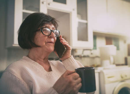 Senior woman holding cup of coffee and talking on mobile phone in kitchen at home