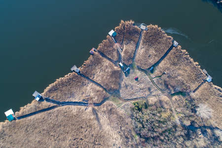 Aerial image of wooden docks with houses on lake with reed around, shoot from drone Archivio Fotografico