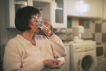 Senior woman sitting in kitchen and drinking pills and water Archivio Fotografico