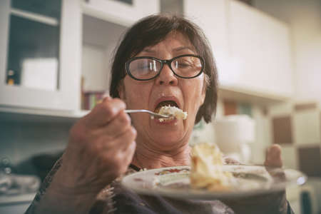 Old woman open mouth to bite tasty cake in kitchen at night. Overeating and addiction to sweets concept
